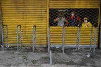 Los empleados de un local cerrado en el mercado de Santa Elena, en Cali (Colombia), aguardan después de que el gobierno ordenó la clausura temporal del mercado. Credit Luis Robayo/Agence France-Presse — Getty Images