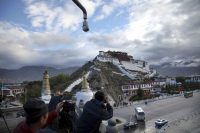 Tourists take photos of the Potala Palace beneath a security camera in Lhasa, capital of the Tibet Autonomous Region of China, on Sept. 19, 2015. (Aritz Parra/AP)