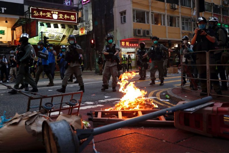 Riot police walk past a fire set by people protesting the new national security law on Wednesday in Hong Kong. (Tyrone Siu/Reuters)