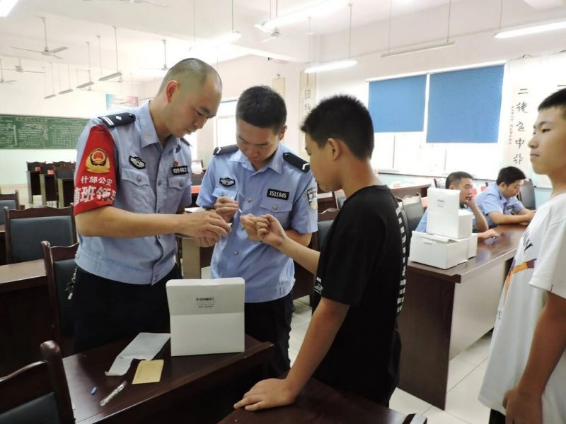 Police officers collecting DNA samples from schoolboys in Shigu, Yunnan Province, in September. Credit The Shifang Municipal People's Government