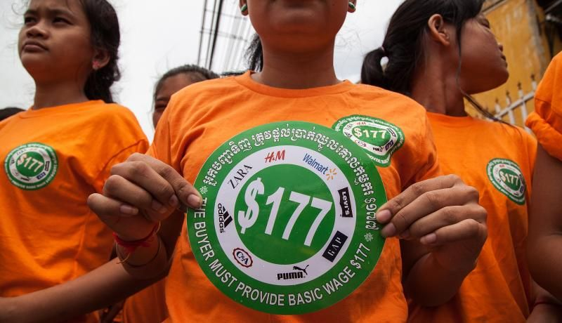 Garment workers hold stickers bearing US$177 during a demonstration to demand an increase of their minimum salary in Phnom Penh, Cambodia. Photo by Omar Havana/Getty Images.