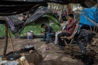 Solicitantes de asilo se sientan en un campamento improvisado para inmigrantes en Matamoros, México. (Alejandro Cegarra/Bloomberg)