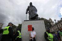 """Agentes de policía custodian una estatua de Winston Churchill mientras un manifestante sostiene un cartel en el que se puede leer: """"¡Enseñen la historia colonial en el colegio!"""", en Londres, el pasado 27 de junio.SIMON DAWSON / Reuters"""