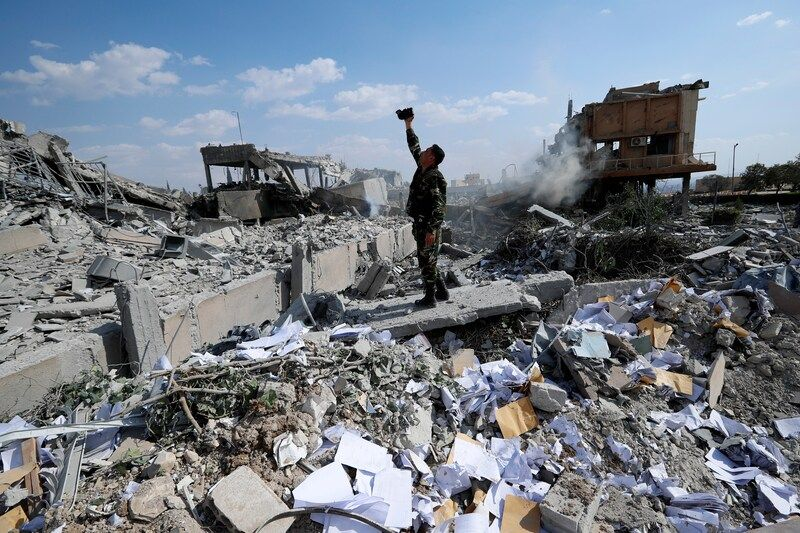 A Syrian soldier films the damage to the Syrian Scientific Research Center in Barzeh, near Damascus, Syria, on April 14, 2018. The site was attacked by U.S., British and French military strikes to punish President Bashar al-Assad for suspected chemical attacks against civilians. (Hassan Ammar/AP)