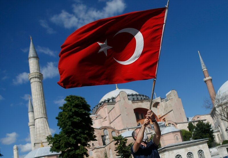 A man waves a Turkish flag outside the Byzantine-era Hagia Sophia, one of Istanbul's main tourist attractions in the historic Sultanahmet district on July 10. (Emrah Gurel/AP)