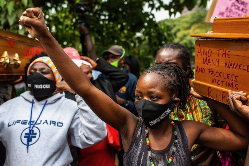 Patrick Meinhardt/AFP via Getty Images The widow of Cosmas Mutethia, who was killed by Kenyan police during a night curfew, helping to bear a symbolic coffin at a protest outside the Kenyan Parliament, Nairobi, Kenya, June 9, 2020