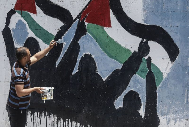 A Palestinian artist paints a mural protesting Israel's West Bank annexation plans in Rafah, in southern Gaza, on July 1. (Said Khatib/AFP via Getty Images)