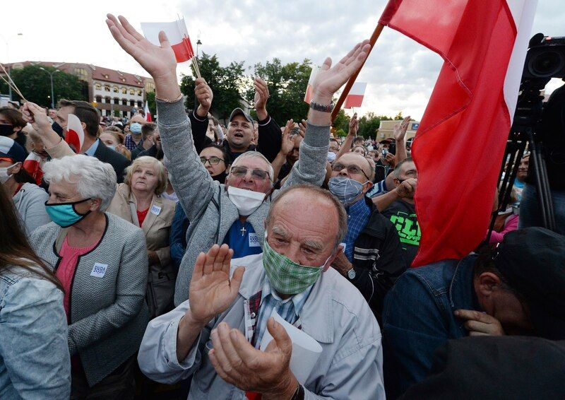 Supporters of Polish President Andrzej Duda wave Polish flags at a campaign rally in Lomza on Wednesday. Duda faces Warsaw Mayor Rafal Trzaskowski in Sunday's runoff election. (Czarek Sokolowski/AP)
