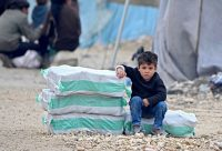 A displaced Syrian boy with packages of humanitarian aid at a camp along the border with Turkey in February. Credit Rami Al Sayed/Agence France-Presse — Getty Images