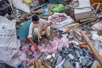A man in New Delhi looks through garbage for valuable items to sell. The pandemic could provide an opportunity to address global income inequality. Credit Yawar Nazir/Getty Images