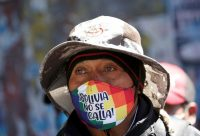 "A man with a face mask reading ""Bolivia will not shut up"" attends a rally demanding the resignation of interim President Jeanine Áñez on Aug. 14 in El Alto, on the outskirts of La Paz. (David Mercado/Reuters)"