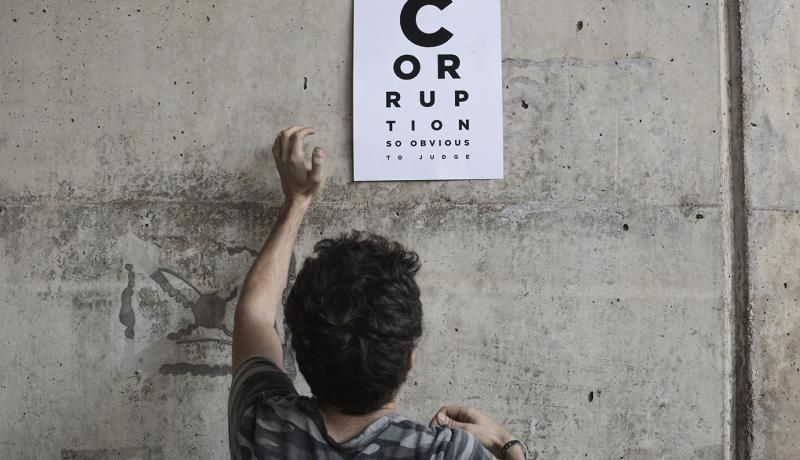 An anti-government protester in Beirut puts up a poster accusing corruption in Lebanon's state judiciary. Photo by Sam Tarling/Getty Images.