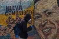 Un hombre con máscaras y guantes protectores pasa por delante de un mural que representa a Hugo Chávez, en el barrio de La Vega en Caracas, el pasado 28 de julio.FEDERICO PARRA / AFP