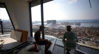 Deux hommes contemplent les ruines du port de Beyrouth le 6 août 2020. — © Patrick BAZ/AFP
