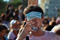 A man smokes a cigarette with his eyes covered by a face mask as he takes part in a protest against the use of protective masks in Madrid on Sunday. (Juan Medina/Reuters)