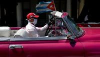 A taxi driver wears a face mask while driving tourists around Havana on 19 March 2020. Photo: Getty Images.