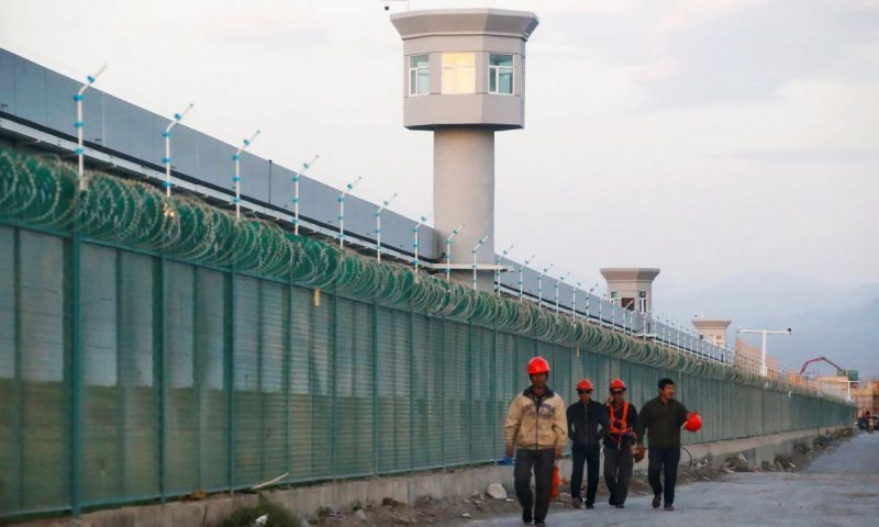 Workers walk by the perimeter of a 'vocational skills education center' in Xinjiang, China. Photograph: Thomas Peter/Reuters