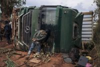 A man looks inside an overturned truck in the middle of National Road 27 in Ituri province in northeastern Congo on Sept. 16. On this road, vehicles travel in convoys escorted by police and soldiers because of recurring attacks by armed militias. (Alexis Huguet/AFP/Getty Images)