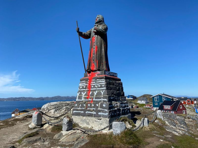 """""""Decolonize"""" is written on the base of the statue of missionary Hans Egede, covered in red paint by Greenlandic activists on June 21. © Christian Klindt Soelbeck / Ritzau Scanpix / AFP"""
