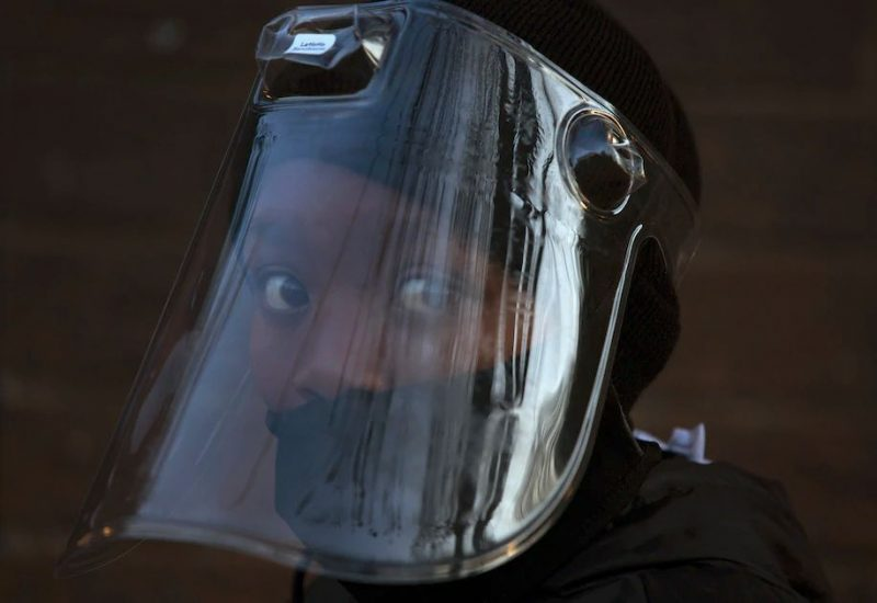 A student wearing a face mask and shield returns to Melpark Primary School in Johannesburg last month. (Denis Farrell/AP)
