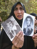 An Iraqi woman shows photographs in May 2003 of her two sons, thought to be killed during late president Saddam Hussein's rule. A trove of Hussein-era files has been returned to Iraq, prompting some to hope of learning the fate of long-lost relatives. (Ahmad Al-Rubaye/AFP/Getty Images)