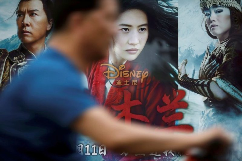 "A man rides past an advertisement promoting Disney's ""Mulan"" at a bus stop in Beijing on Wednesday. (Carlos Garcia Rawlins/Reuters)"