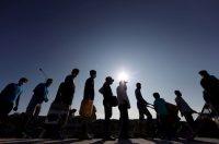 Refugiados y migrantes del campo de Moria hacen cola para entrar en un nuevo campamento en la isla de Lesbos. REUTERS/Yara Nardi