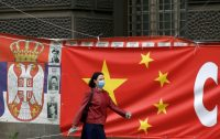 A woman passes a tarp emblazoned with a Chinese flag on a street in Belgrade, Serbia, on April 13. (Darko Vojinovic/AP)