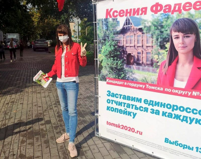 Ksenia Fadeyeva, who won a seat on the city council in Tomsk, Russia, on Sunday, is seen next to one of her campaign posters in the Siberian city last month. (Andrei Fateyev/AP)