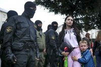 A woman with her child watches in Minsk on Sept. 8, 2020, as police officers detain protesters during a rally for the detained Maria Kolesnikova, a member of the opposition Coordination Council that is seeking talks with President Alexander Lukashenko on a transition of power in Belarus. (AP) (AP)