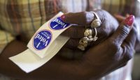 """A poll station official holding """"I Voted"""" stickers in South Carolina. Photo by Mark Makela/Getty Images."""