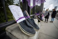 A written message is seen attached to a pair of shoes as part of a memorial for drug overdose victims in Vancouver on Aug. 31. (Darryl Dyck/The Canadian Press, via AP)