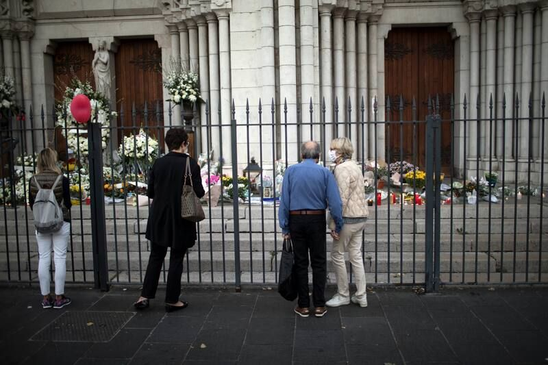 People outside the Basilica of Notre-Dame de L'Assomption in Nice, France, pay their respects on Friday to those killed during a knife attack at the church a day earlier. (Daniel Cole/AP)