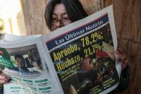 A woman reads a newspaper showing the results of the previous day's referendum in favor of rewriting the nation's constitution in Santiago, Chile, on Oct. 26. (AP Photo/Esteban Felix)
