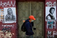"""A man walks by posters of """"Star Wars"""" characters Chewbacca and Han Solo reading """"I Approve"""" in reference to the Oct. 25 referendum to change Chile's military dictatorship-era constitution, in Santiago on Wednesday. (Martin Bernetti/AFP/Getty Images)"""