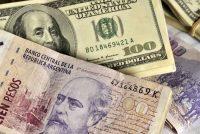 Una foto de 2010 de billetes de 100 pesos argentinos y billetes de 100 dólares estadounidenses. (Diego Giudice/Bloomberg)