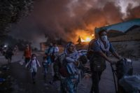 Refugees and migrants flee fire at the Moria camp on Lesbos in September. Successive fires made 12,000 inhabitants homeless (AP Photo/Petros Giannakouris) Photograph: Petros Giannakouris/AP