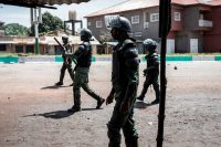Police officers walk toward demonstrators during mass protests after preliminary results were released in Conakry, Guinea, on Oct. 23. (John Wessels/AFP via Getty Images)