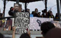Una manifestante sostiene un cartel en apoyo a Black Lives Matter en una protesta contra la violencia policial en Massachusetts en junio de este año. Credit Cj Gunther/EPA vía Shutterstock