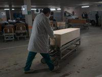Un trabajador sanitario lleva un ataúd a un estacionamiento en Barcelona que se usó para albergar a víctimas de la COVID-19. Credit Samuel Aranda para The New York Times