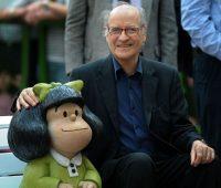 En esta foto del 30 de agosto de 2009, el caricaturista argentino Joaquín Salvador Lavado, conocido como Quino, posa al costado de una escultura de su personaje, Mafalda, en Buenos Aires, Argentina. (Alejandro Pagni/AFP via Getty Images)