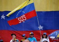 """Un partidario del líder opositor venezolano Juan Guaidó, ondea una bandera venezolana marcada con las letras """"SOS"""", durante una manifestación en Caracas, Venezuela, el sábado 11 de mayo de 2019. (AP Photo/Fernando Llano)"""