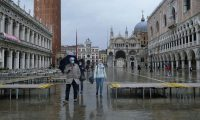 People walk in St. Mark's Square, Venice, during high tide on 15 October, as the Mose flood barriers are raised for the second time, successfully protecting the lagoon city from flooding. Photograph: Manuel Silvestri/Reuters