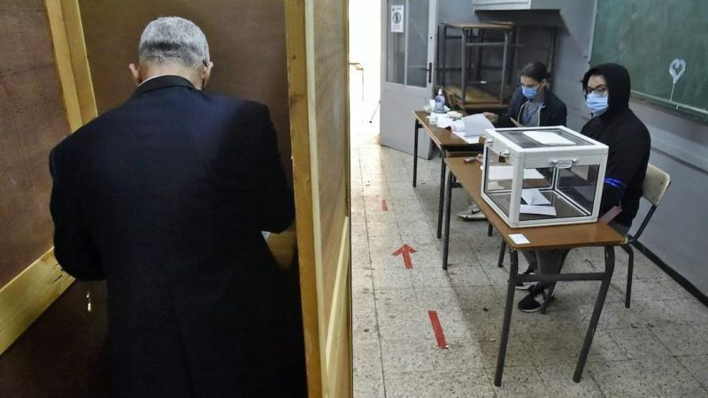 An Algerian man prepares to vote at a polling station in the capital Algiers during a vote for a revised constitution, on 1 November 2020. RYAD KRAMDI / AFP