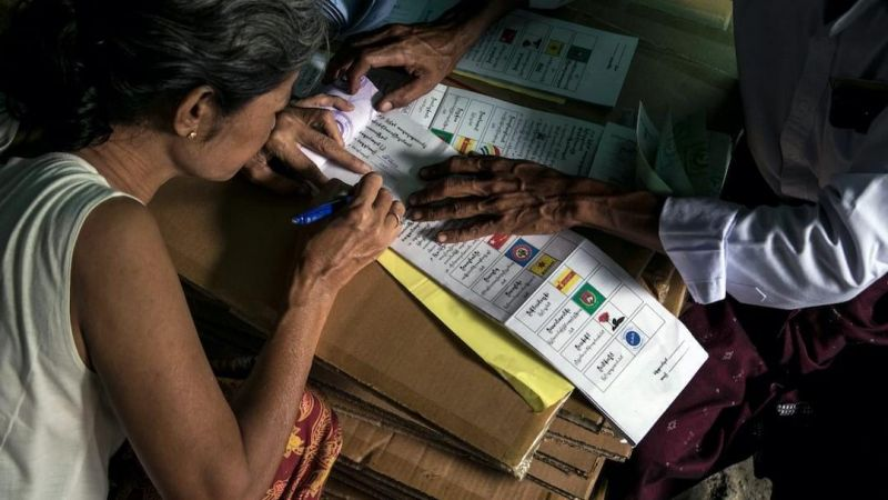 A woman casts her vote at a mobile polling station inside her home in Yangon on 29 October, 2020, as advance voting in the country's elections began for elderly people. Sai Aung Main / AFP