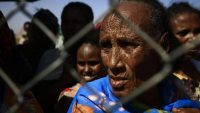 An Ethiopian refugee who fled fighting in the Tigray Region looks on from behind a fence as she waits with others at the Village 8 border reception center in Sudan's eastern Gedaref State, on 20 November 2020. ASHRAF SHAZLY / AFP