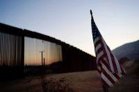 Una bandera estadounidense descansa justo al norte de una nueva sección del muro fronterizo cerca de Tecate, California. Este escenario se ha vuelto un símbolo de la xenofobia de Trump, un ataque a la migración (Gregory Bull/AP)