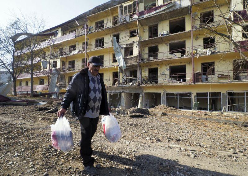 Un hombre pasea por delante de un edificio bombardeado en Shushá.AP