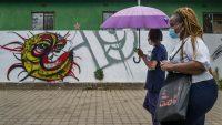 Des passantes devant un graffiti représentant le coronavirus à Soweto, en Afrique du Sud, le 19 novembre 2020. — © keystone-sda.ch