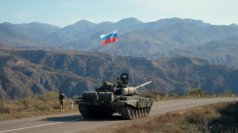 A service member of the Russian peacekeeping troops walks near a tank near the border with Armenia, following the signing of a deal to end the military conflict in the region of Nagorno-Karabakh, 10 November 2020.